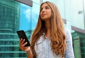 Young Serious And Determined Business Woman Standing In Front Of Modern Building With Phone In Her H poster