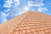 Roof Tiles And Sky Sunlight. Roofing Contractors Concept Installing House Roof. poster