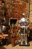 stock photo of bric-a-brac  - A collection of objects outside a Tuscan junk shop including armour a crossbow and arrows - JPG