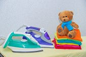 Iron And Baby Clothes. Colored Clothes On An Ironing Board. Bright T-shirts. Ironed Colored Baby Und poster