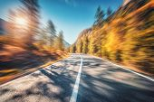Mountain Road In Autumn Forest At Sunset With Motion Blur Effect. Asphalt Road And Blurred Backgroun poster