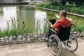 Disabled Man In Wheelchair Having Fun While Resting Using A Tablet Computer At Park, Concept Of Tech poster