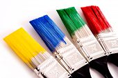 picture of paint brush  - A row of primary colored paint brushes on white background with copy space - JPG