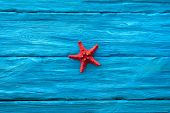 Red Starfish On Blue Wooden Table Background. Sea Travel Concept. poster