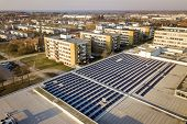 Aerial View Of Blue Shiny Solar Photo Voltaic Panels System On Commercial Roof Producing Renewable C poster