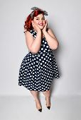 Cute Portrait Of A Full-length Red-haired Woman Plus Size In A Retro Polka-dot Dress, Joyful Smiling poster