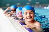Portrait Of Children In Water At Edge Of Pool Waiting For Swimming Lesson poster