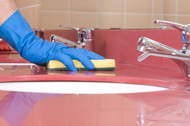 image of house cleaning  - a worker is Cleaning red Bathroom Sink - JPG