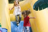 stock photo of inflatable slide  - Two beautiful little girls having fun on inflatable playground - JPG