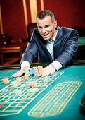 Gambler stakes playing roulette at the gambling house. Risky entertainment of gambling