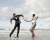 Image of businesspeople hanging on strings like marionettes against sea background. Conceptual photo