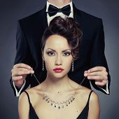 stock photo of red-necked  - Elegant man on a beautiful woman wears a necklace - JPG