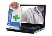 stock photo of dispenser  - Internet drug store concept doctor holding prescription medicine through a laptop screen - JPG
