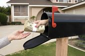 image of bundle money  - A bundle of cash is being delivered to a homeowner waiting for an economic stimulus payment or property bailout money - JPG