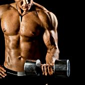 stock photo of dumbbells  - very power athletic guy execute exercise with dumbbells on black background - JPG