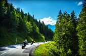 Bikers in mountainous tour, traveling across Europe, curve highway in mountains, scene destinations,