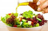 Fresh salad with olive oil isolated on white background, pouring salad dressing into cutting vegetab