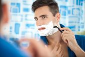 stock photo of razor  - Close up of a young man shaving using a razor - JPG