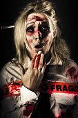 image of mortuary  - Evil zombie woman expressing fear and  horror when awakening in a morgue wrapped in fragile postage tape - JPG