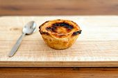 stock photo of custard  - Pastel de nata Portugeuese custard tart with spoonb
