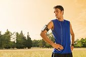 image of jogger  - Portrait Of Male Jogger Standing In Field While Listening Music - JPG