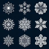 White snowflake ornate shapes isolated on dark blue background.