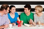 stock photo of eatables  - Cheerful family of four relishing delicious eatables and dessert - JPG