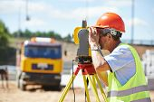 stock photo of theodolite  - Portrait of builder worker with theodolite transit equipment at construction site outdoors during surveyor work - JPG