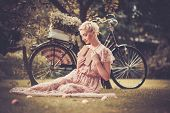 image of poetry  - Dreaming blond retro woman with a book in summer dress sitting on a meadow - JPG