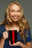stock photo of thermos  - Positive young woman with long hair and blue eyes holding thermo mug - JPG