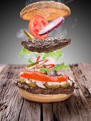 stock photo of cheese-steak  - Delicious hamburger on wooden background - JPG