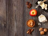 stock photo of ingredient  - Ingredients for apple pie cooking. Fresh red apple butter flour brown sugar nuts and spices on a rustic wooden background.
