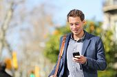 image of sms  - Young urban businessman professional on smartphone walking in street using app texting sms message on smartphone wearing jacket on Passeig de Gracia - JPG
