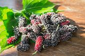 foto of mulberry  - heap of mulberry fruit and leaf on wooden table - JPG