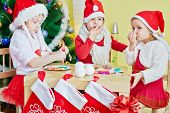 Two little girls and one boy in santa caps play in food sitting at wooden table with attached socks