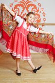 Smiling girl in red folk costume dances with shawl near wall with pattern