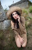 stock photo of nu  - Portrait of a girl in a straw hat against background of nature and old concrete wall - JPG