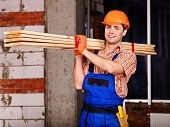 stock photo of millwright  - Happy man in builder uniform carry boards indoor - JPG