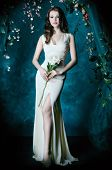 foto of loach  - Beautiful young woman standing under an arch of flowers and overgrown loach - JPG
