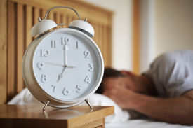 stock photo of fatigue  - Man sleeping with alarm clock foreground concept for morning - JPG