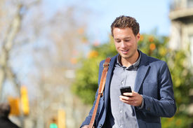 stock photo of jacket  - Young urban businessman professional on smartphone walking in street using app texting sms message on smartphone wearing jacket on Passeig de Gracia - JPG
