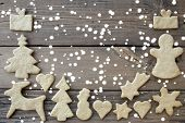 stock photo of ginger bread  - Ginger Bread Cookies building Frame on Wood in the Snow as Food Background with Copy Space - JPG