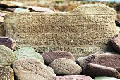 stock photo of nepali  - Mani wall and stones with buddhist symbols - JPG