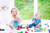 stock photo of sisters  - Adorable laughing toddler girl and a funny little baby boy brother and sister playing with colorful blocks sitting on a floor in a sunny bedroom with a big window - JPG