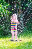 stock photo of sprinkler  - Funny laughing little girl in a colorful swimming suit running though garden sprinkler playing with water splashes having fun in the backyard on a sunny hot summer vacation day - JPG