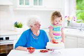 picture of granddaughter  - Happy senior lady loving grandmother baking a homemade strawberry cake with her granddaughter adorable curly toddler girl in a colorful summer dress in a white modern kitchen with window - JPG