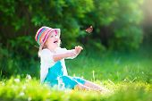image of summer insects  - Happy laughing little girl wearing a blue dress and colorful straw hat playing with a flying butterfly having fun in the garden on a sunny summer day