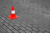 stock photo of road sign  - plastic traffic cone on a bricked area - JPG