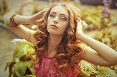 stock photo of diva  - Portrait of beautiful young woman with makeup in fashion clothes on nature - JPG