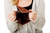 stock photo of payday  - Young caucasian woman with empty wallet  - JPG